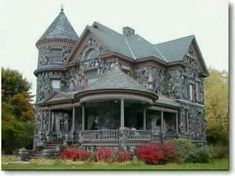 Victorian house built with stones, making it look like a tiny castle. I love the tower and the gazebo-like porch