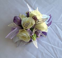 White roses with purple accent and sparkles on a wrist corsage