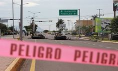 A red line prevents access to burned vehicles, part of a Mexican military convoy, which was ambushed by gunmen in Culiacán, Sinaloa, on 30 September.