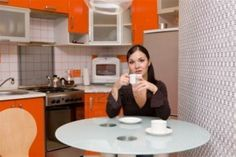 a woman was enjoying a comfortable atmosphere in the kitchen with a dominant orange shades