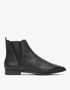 From Jeffrey Campbell, a sleek leather ankle boot in black matte. Features pointed toe, snake-skin-textured leather uppers, side elastic detail, pull tab, man made sole, and small stacked heel. • Leather ankle boot in black matte • Pointed toe • Sna