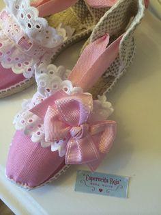 Detalle de foto. Alpargatas planas con cintas en color rosa, tira doble bordada blanca y lazote rosa a juego.