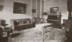 1920s parlor. Rugs! Bizarrely small furniture? great table, piano