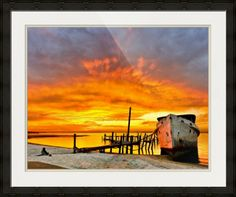 """""""Old Boat Yellow Red Sunrise Fine Art Giclee Prints"""" by Eszra Tanner, navarre, fl // a dark red sunsrise behind an old boat and broken pier.  Landscape taken near Navarre Beach, Florida.  Fine art giclee prints available. // Imagekind.com -- Buy stunning fine art prints, framed prints and canvas prints directly from independent working artists and photographers."""