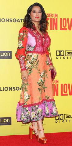 Salma Hayek isn't afraid of color. The actress stunned in a floral print dress with red lace trim and front lace-up detail. Hayek styled the supersaturated dress to perfection with bright orange satin heels, a velvet clutch, and showstopping jewels.