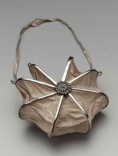 Heptagonal bag. French, about 1800. Old rose moiré silk panels on steel cockade frame. Cut steel rosettes at rivets.