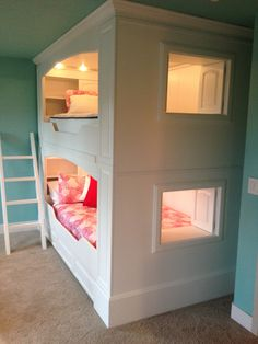 Queen bunk beds with built in shelving, windows, and individual lights.