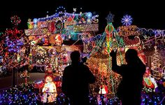 People take photos of colourful Christmas lights in front of a house in Toronto, Canada  //   Xinhua /Landov / Barcroft Media