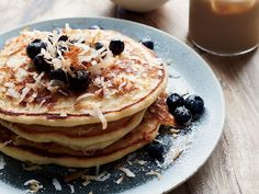 Coconut Pancakes | Shredded coconut, sprinkled onto the batter and then layered in between, is key to these sensational, tropical-flavored pancakes.
