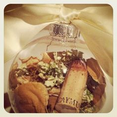 Looking for a way to save your wedding bouquet? Make a Christmas ornament! This is a great idea for those of you who don't want to save the entire bouquet. Gather a few petals from your bouquet, a cork from the wine served at your wedding, and top it off with a gorgeous colored ribbon! You can even write the date of your wedding on the glass ornament.