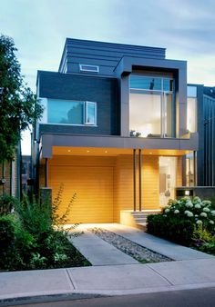 Beautiful Exterior Ideas for Modern House Design : Small Modern House Design With Flat Roof And Hidden Front Door Plus Modern Wood Siding And Garage Door Also Glass Windows Plus Outdoor Lighting And Concrete And Gravel Driveway