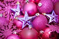 a festive holiday background with pink coloured glittery christmas tree ornaments on a bed of sparkling tinsel
