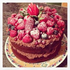 Chocolate cake with chocolate butter icing topped with strawberries, raspberries and blueberries
