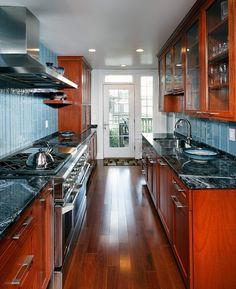 Love these colors, cherry cabinets, black & white granite and blue subway tile backsplash.
