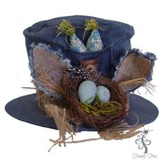 Denim Bunny Hat Easter Decoration Denim Bunny Hat with wired ears, decorated with burlap, raffia, small twig bird nest with blue eggs, stuffed carrots in a blue floral print and buttons.