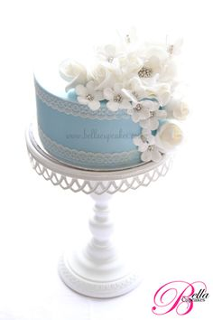 Baby blue single-layer wedding cake with white lace trim and sparkly white flowers.