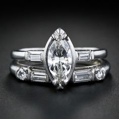 This is a classic mid-century wedding set in platinum. A .56 carat marquise cut diamond is illusion set and flanked with baguette on either side. The matching wedding band fits perfectly next to the ring and features a mix of round and baguette cut diamonds. Tailored elegance.