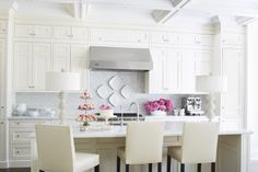 White washed kitched with marble table top, tiled walls, upholstered chairs and table lamps designed by Plum Furniture