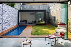 Porche trasero de la vivienda con piscina y pequeño jardín. Por CR2 Arquitetura