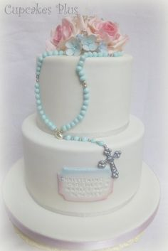 "This cake is for a joint christening for a boy and girl hence the blue and pink colors. It's a 5"" and 7"" chocolate cake filled and covered with chocolate ganache"