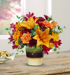 What a bounty! This mix of radiant autumnal #roses and #lilies is the gift that keeps on giving presented in a pretty-meets-practical stoneware crock with reactive glaze. This bouquet includes orange bi-color roses, orange asiatic lilies, rust cushion spray #chrysanthemums, bronze daisy spray chrysanthemums, yellow button spray chrysanthemums, seeded #eucalyptus, parvifolia eucalyptus, and preserved #OakLeaves. Delivered in Telefora's Thankfully Yours Crock. Starting at $59.99