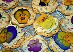 Edible Flower Canapes   •½ cup snipped fresh dill or chive leaves  •1 pound natural cream cheese softened  •2 large loaves of dense sandwich or rustic-style unsliced bread or 2 packages melba toast  •A selection of edible flowers, 4 or 5 dozen:  nasturtiums, borage, calendulas, pineapple sage, runner bean flowers, pansies, violas, violets, gem marigolds. • Herb leaves:  sage, parsley, mint, dill, and basil
