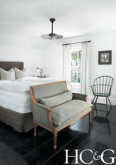 Cozy Sag Harbor bedroom with antique French settee at the foot of the bed; #Hamptons; #Windsor chair