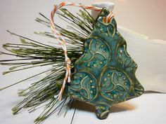 This ornament is made of white stoneware clay and hand decorated. Glazed in teal and green.