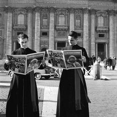 A pair of priests read 'L'Osservatore' outside St Peter's Basilica in Vatican City. Circa 1955. Evans/Three Lions / Getty Images