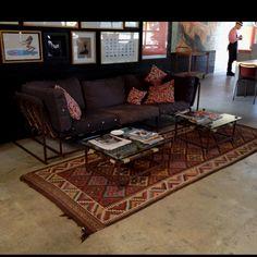 Concrete floor with rug and metal frame sofa in the Deus shop, LA