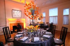 The gray tabletop decor in one of the dining areas of Phillips Collection's 90th anniversary gala provided a striking contrast to the tall orange and yellow floral arrangements by Jack Lucky Floral Designs.