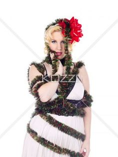 close shot of a clumsy christmas wrapper - Girl wrapped up in holiday decorations on white. MUA and Model: Amanda Wynne