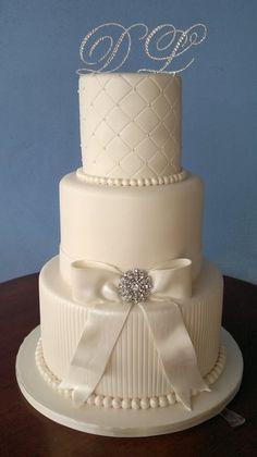 Torta de boda de color blanco de tres niveles, con distintos diseños por cada nivel, decorada con perlas y un broche, muy vintage. #TortasDeBodas
