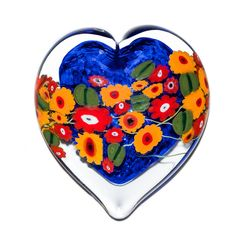 California Poppy on Blue Heart Paperweight by Shawn Messenger. This hand-formed, heart-shaped glass paperweight has a background of dark blue chips that are encased with a ring of clear glass. The red and orange California poppies along with the leaf millefiore are created individually by the artist using ancient glass techniques. The floral design floats on the surface of the heart from one side to the other. Each piece is unique. Patterning and dimensions may vary slightly.