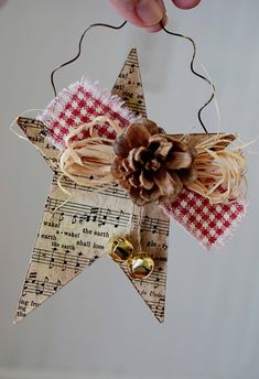 This is a tin star with pages from an old hymnal mod podged to it's front, then decorated with bells, ribbon and a pine cone.