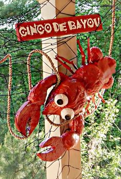 Paper mâché crawfish. Balloons covered in mâché for body and eyes. Cereal box pieces cut and hot glued for legs and claws. Wire hanger cut for antennas. Crab boil, crawfish boil decor.