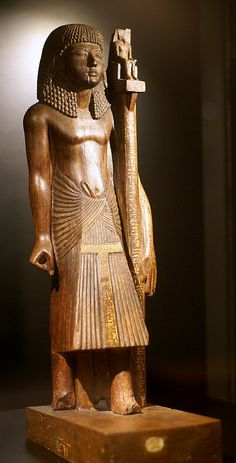The wooden figure shows Nebanen, a writer from Deir el-Medineh. He wears a long braided wig and a wrap skirt. In his left hand he holds a banner, on which sits a figure of the god Amun-Re.