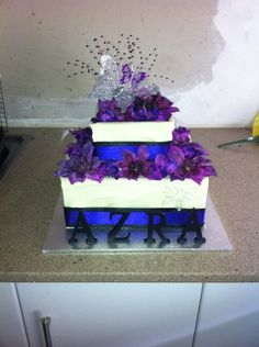 Birthday or wedding cake - White chocolate sided cake with butter cream icing over a butter cake with tri coloured layers in purples and black and decorated with artificial flowers.