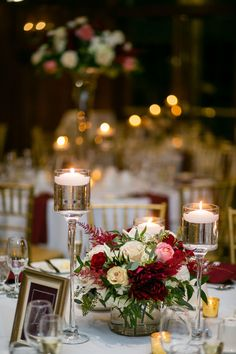 A lush low centerpiece filled with greenery and pops of wine, champagne and ivory blooms surrounded by candles. See more wedding inspiration on our website now! Romantic Wedding Receptions, Wedding Reception Planning, Event Planning, Wedding Events, Low Wedding Centerpieces, Floral Centerpieces, Wedding Decorations, Quinceanera Centerpieces, Floral Wedding