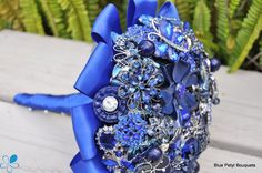 Blue Brooch Bouquet BB08 - This brooch bouquet features new and vintage navy and royal blue brooches. The bouquet is finished with a blue ribbon collar and handle with white pins. You can keep and display your heirloom bouquet for ever after.