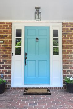 Blue door with white trim and black accents (door knocker, doorbell, door handle)