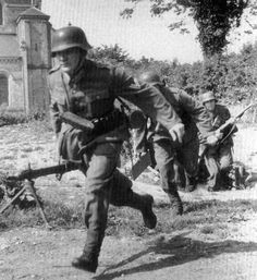 German Soldiers of the 709 Infantry Division, abandon their refuge and rush to their positions in Montebourg, Normandy in June 1944.