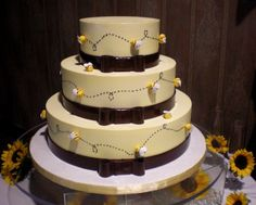 A lot of Bees Wedding Cake - Cake size : 16, 12 & 8, swiss butter cream frosting, bows and bee made out of fondant.