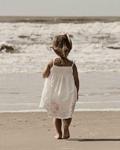 Cute little girl in the sun in a sundress