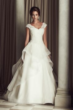 French Alençon Lace and Organza bridal gown. Beaded v-neck drop waist lace bodice with cap sleeves. Full organza skirt with cascading mohair detailed edging. Chapel Train. Style 4458. By PalomaBlanca