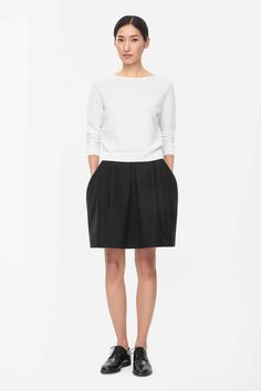 This skirt!!!!! COS - BOXY PLEATED SKIRT  Made from a thick cotton-mix that is lightly textured, this flared skirt has boxy folds at the waistline for a structured silhouette. With a concealed back zip and loose pockets, it is designed to sit on the waist.