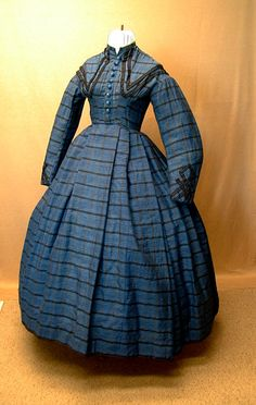 beautiful fabric! - Wool Plaid Dress, 1860s - Hand sewn, made from lightweight wool in blue/black plaid. The dress is piped at the armsyces and waist; bodice is darted but stayed; sleeves are two piece coat style with wide elbows. Center front closure with hooks and eyes, the 9 velvet covered buttons are decorative. The skirt is box pleated in the center front with tight cartridge pleating on the sides and back; there is also a pocket in the right front/side.
