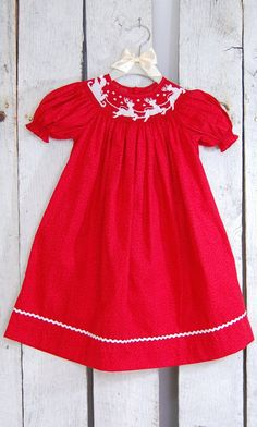 A beautiful Christmas smock dress with amazing Santa and reindeer embroidery to accent the neck will make any little girl feel like Santa is right around the corner. 100% Cotton, Machine Washable
