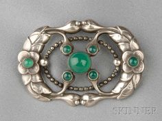 .830 Silver and Green Onyx Brooch, Georg Jensen, designed by Georg Jensen, with floral motifs set with seven cabochon green onyx, lg. 2 1/8 in., no. 76, signed GI, Denmark.