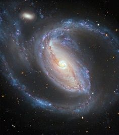 The Seyfert galaxy NGC 1097, in the constellation of Fornax (The Furnace), is seen in this image taken by ESO's Very Large Telescope (VLT). A tiny elliptical companion galaxy, NGC 1097A, is also visible at the top left.  NGC 1097, the larger galaxy, also has four faint jets — too faint to be seen in this image — that emerge from its center, forming an X-shaped pattern, and are the longest visible-wavelength jets of any known galaxy.